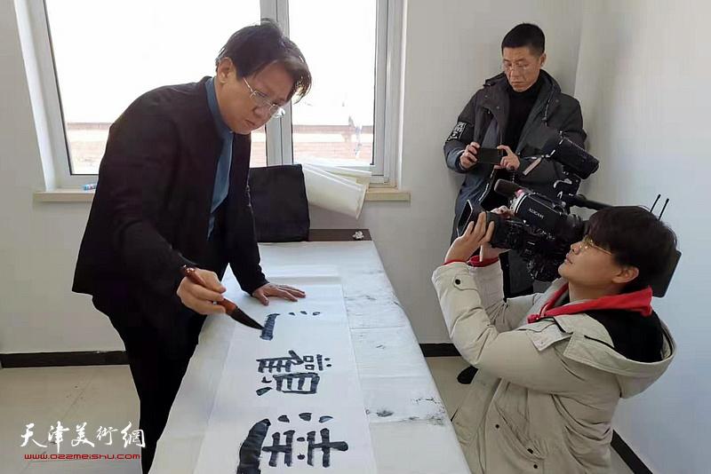 李毅峰在活动现场写书法。