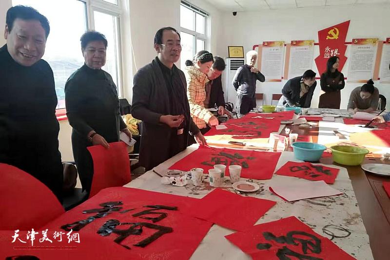卞昭宏、杨利民、于文在活动现场写福。