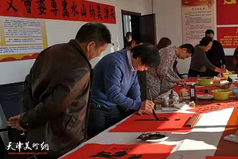路洪明、姜金军在活动现场写福。