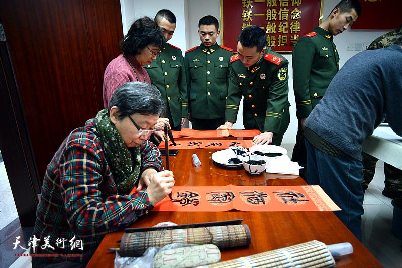 许鸿茹在慰问现场写春联。
