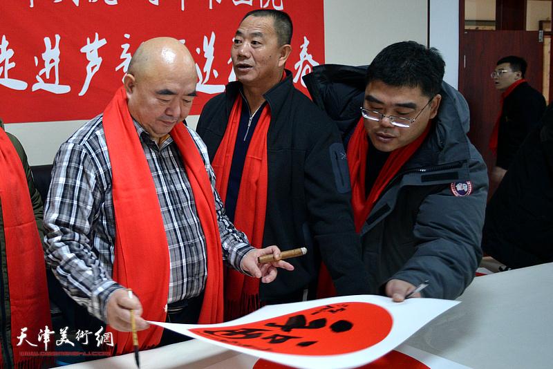 尹沧海在送福迎春活动现场写福字。