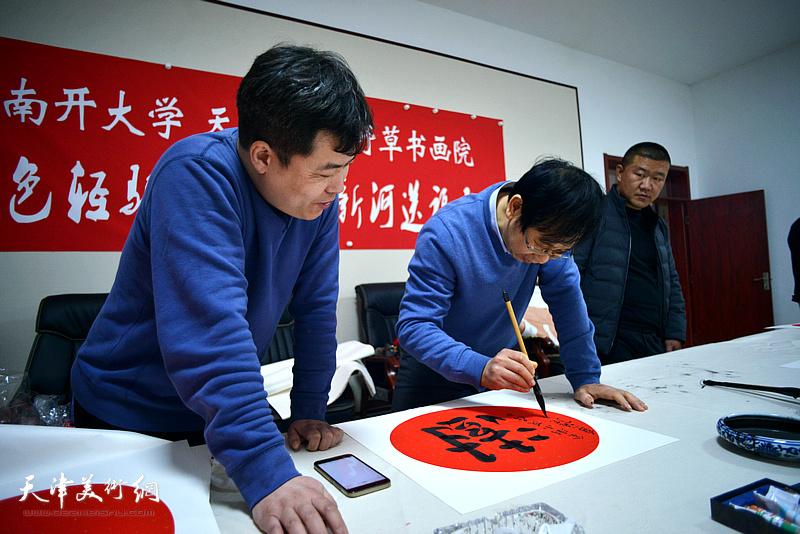 路洪明在送福迎春活动现场写福字。