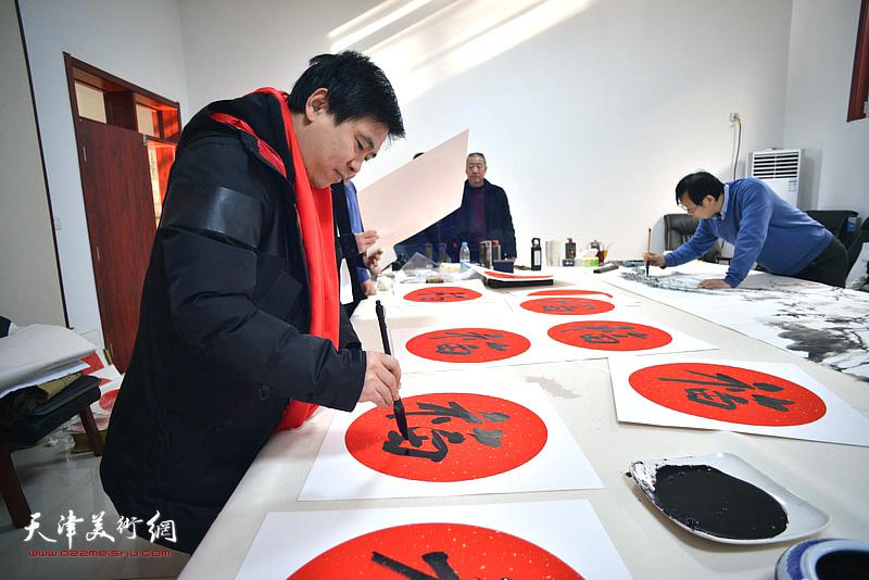 陈志峰在送福迎春活动现场写福字。