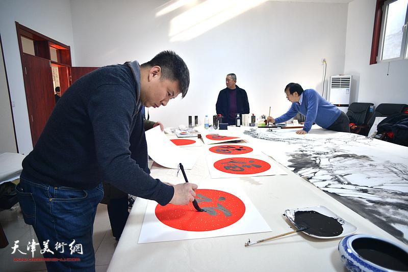 刘远征在送福迎春活动现场写福字。