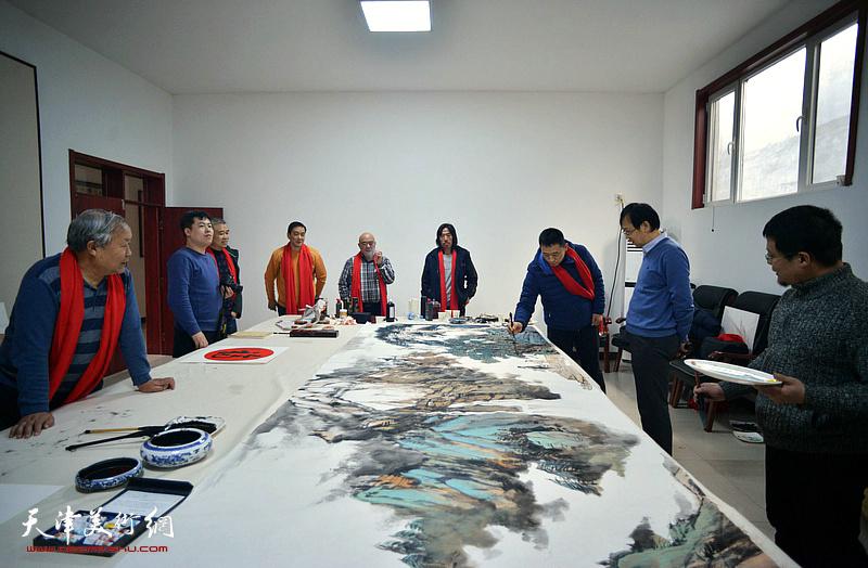 书画家们在送福迎春活动现场创作巨幅山水画《高山仰止》。