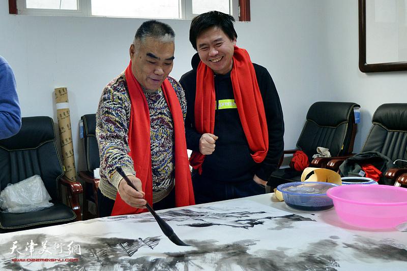 林德谦、陈志峰在创作巨幅山水画《高山仰止》现场。