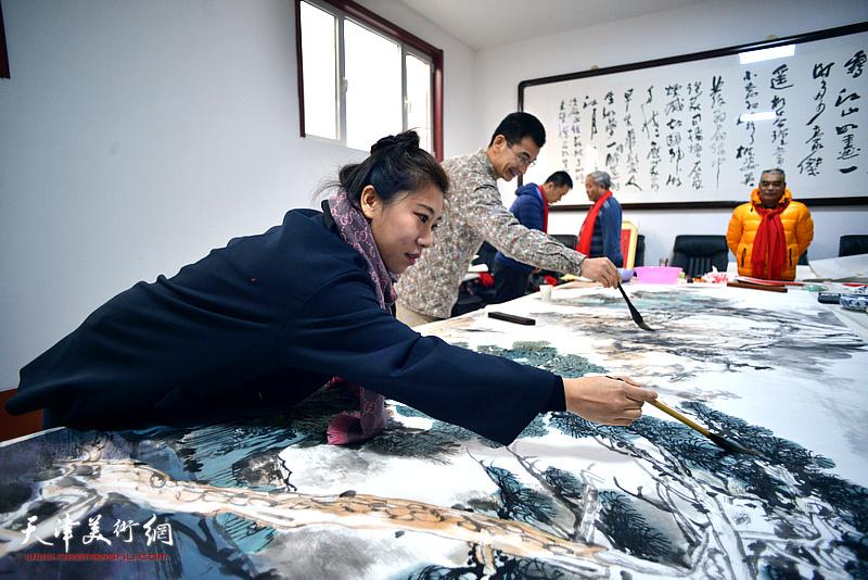姜金军、张琳在创作巨幅山水画《高山仰止》现场。
