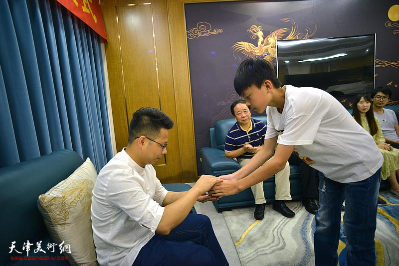 新弟子王昊泽向师傅屈建辉敬茶。