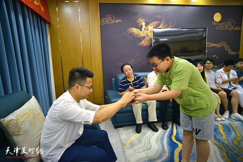 新弟子刘家轩向师傅屈建辉敬茶。