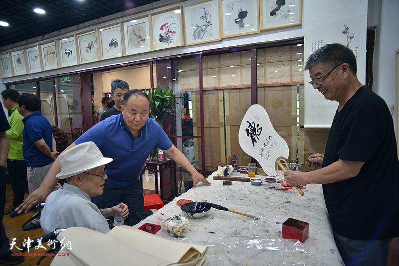 孙长康在画展现场与书法家张文荪交谈。