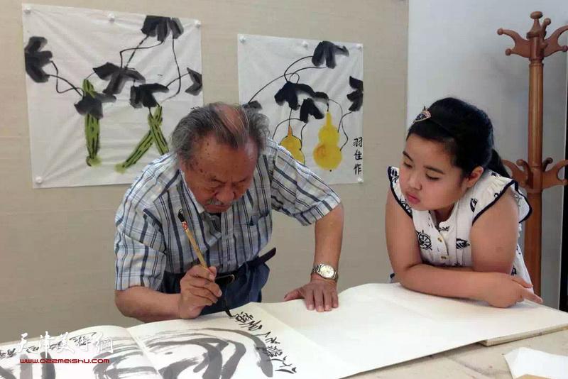 2015年吴燃先生与羽佳小朋友在写画。