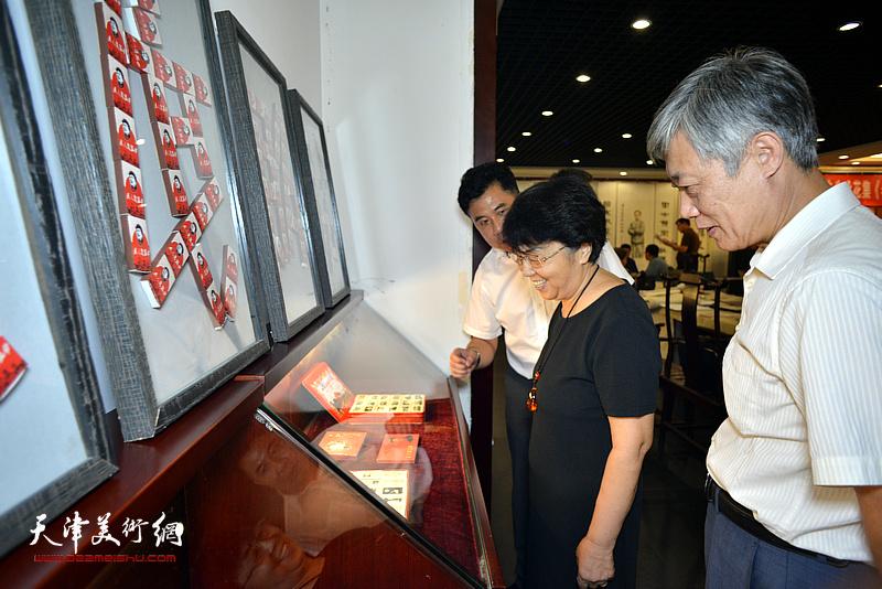 王善全向李润兰、李培隽介绍展出的火花展品。