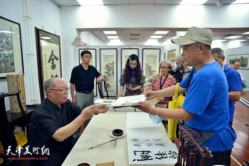 李家尧在展览现场为读者签名售书。