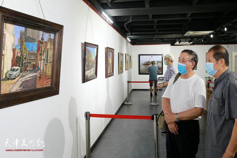 郭凤翔、孙维观赏展出的画作。