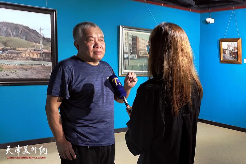 万栩在画展现场接受媒体采访。