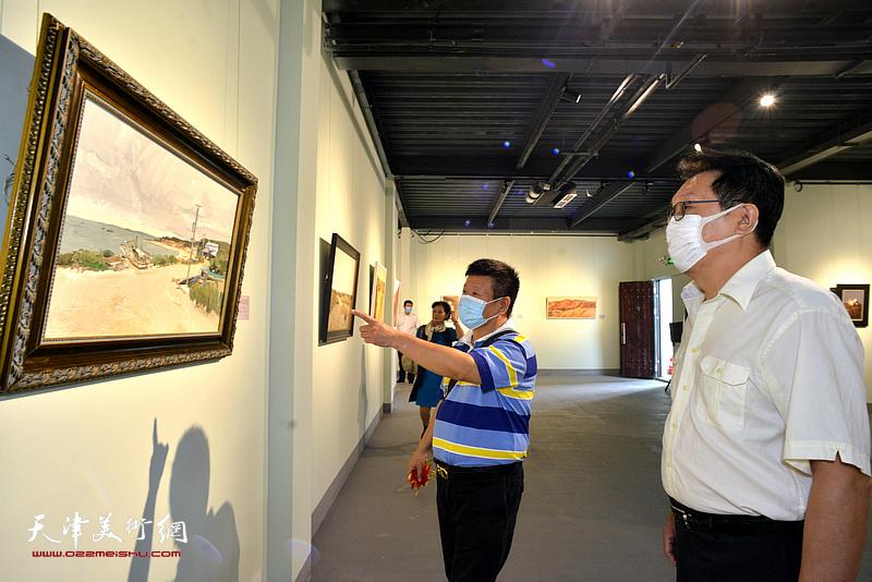 刘书瀚、帅起观赏展出的作品。