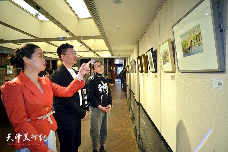 叶武与来宾一起观赏展出的画作。