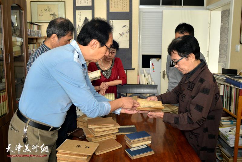 萧惠珠、哈铭、李文祥、哈敏观赏哈珮先生劫后存书。