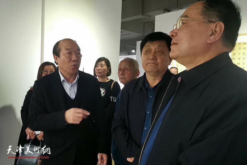 王树秋在书法作品展现场为嘉宾讲解展出的作品。