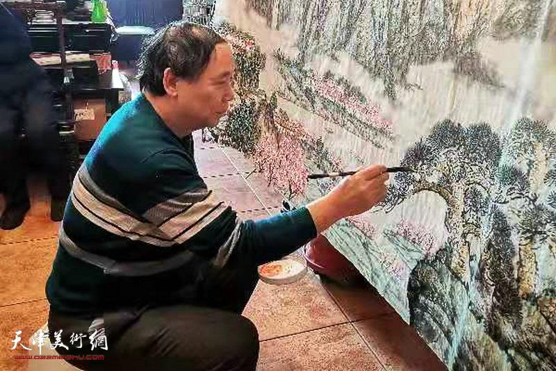 郭凤祥先生在创作巨制国画《绿水青山,小康家园》。