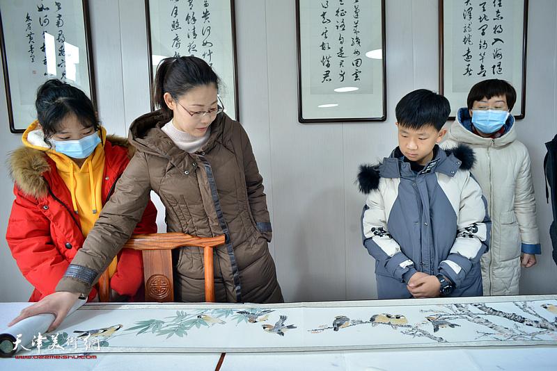 冉萍观赏怀德书院小画家司佟宇的花鸟长卷。