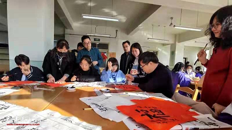 刘镪、赫英杰、许洁、赵文静辅导藏族同学写福字。