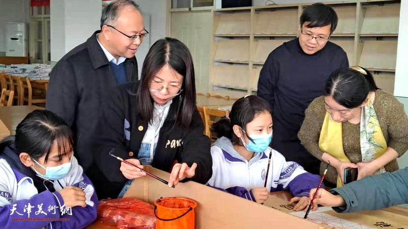 庄雪阳、刘镪、赵文静辅导藏族同学写福字。