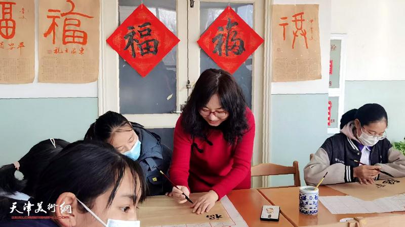 赫英杰辅导藏族同学写福字。