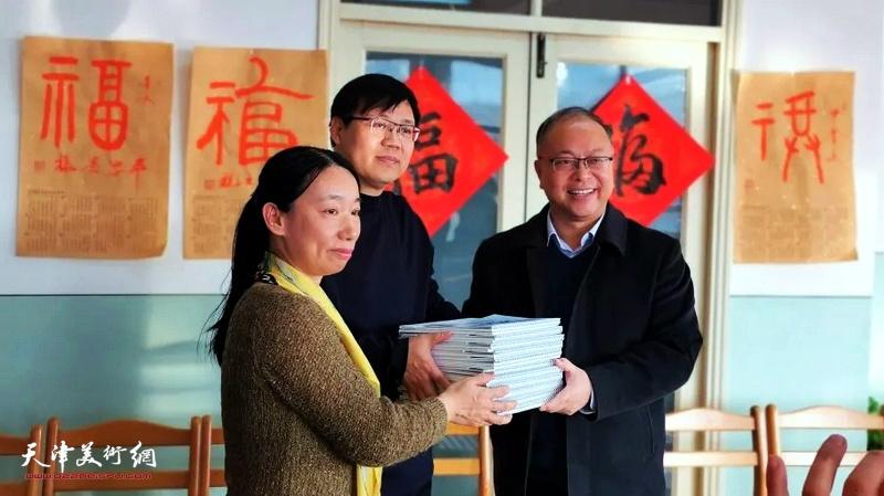 庄雪阳、刘镪代表天津市书画艺术研究会青年书画艺术研究院向天津七中赠送台历。