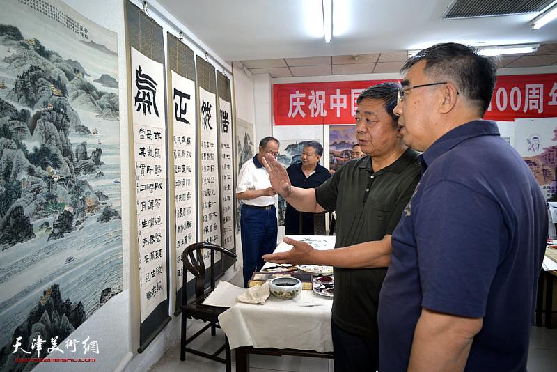 原红桥区政协副主席由明胜与来宾观赏展出的陈连羲书画作品。
