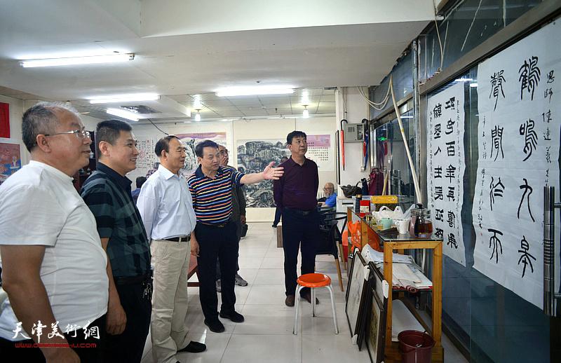 书法家孟新民向来宾介绍展出的陈连羲书画作品。