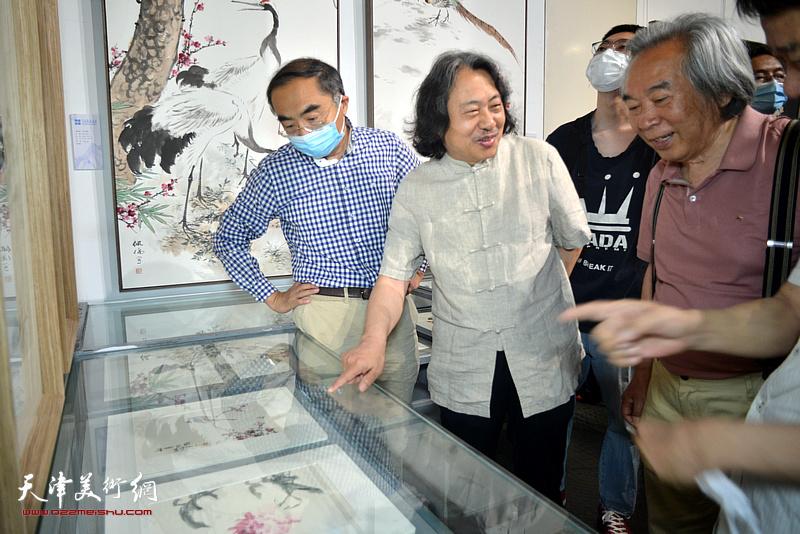 贾广健、霍春阳、喻建十、刘文生在展览现场观看作品。