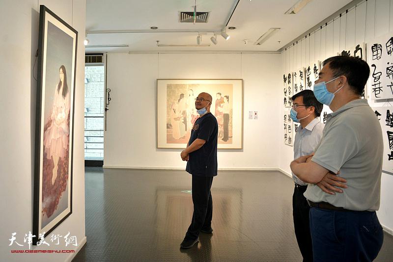 靳风辉、李鑫、于小冬在展览现场观看作品。