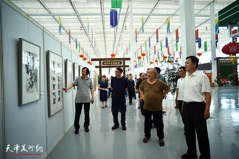 中国美术家协会副主席、天津市美术家协会主席王书平在滨海国际花卉科技园区观看展出的阚传好作品。