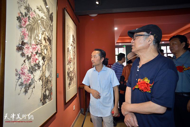 郭书仁、安士胜观赏展出的作品。