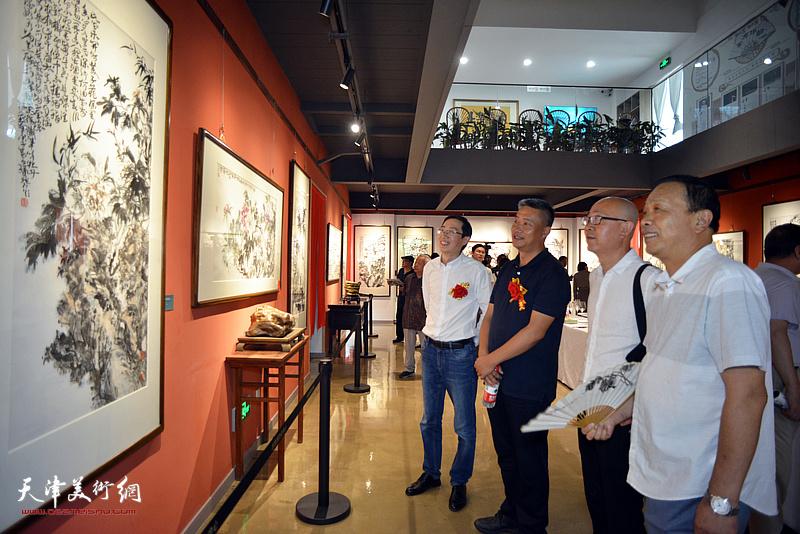 左起:李传凤、高文清、马驰、赵德昌观赏展出的作品。