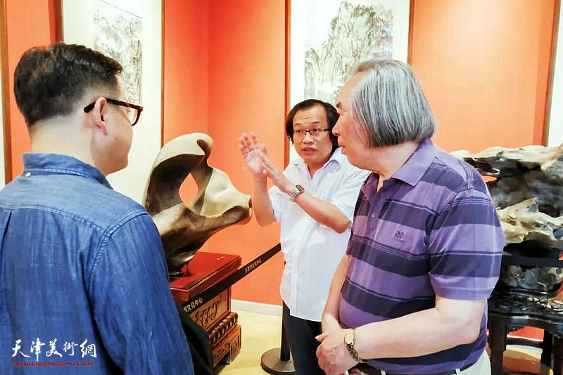 杨惠东向霍春阳介绍展出的作品。