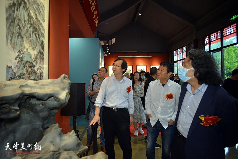 贾广健、刘文生、路洪明观赏展出的作品。