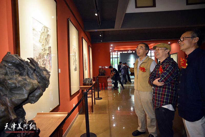 陈福春、喻建十、何东观赏展出的作品。