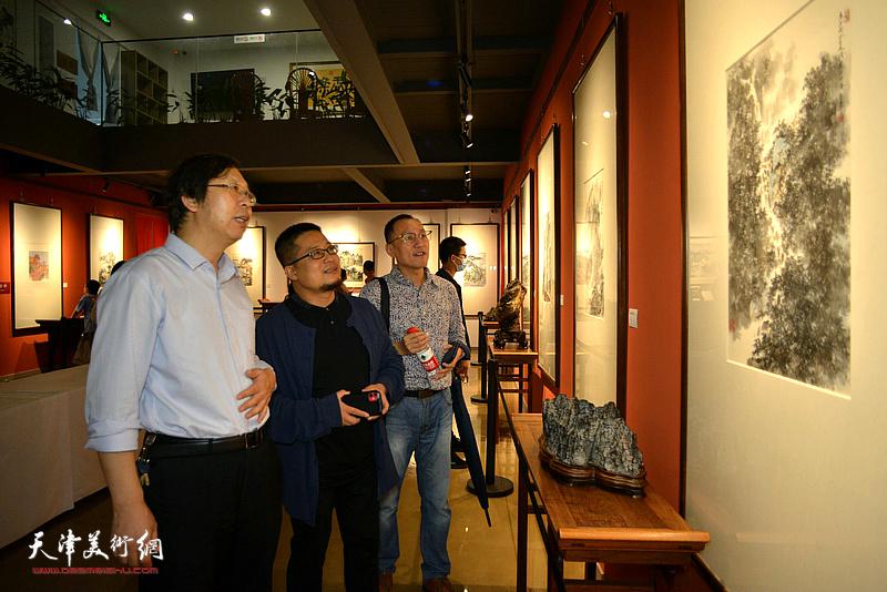 路洪明、闫勇、曹祥哲观赏展出的作品。