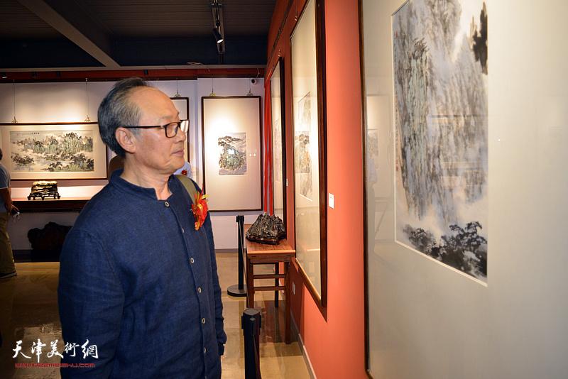 陈福春观赏展出的作品。